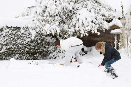 29565663 - father and son shoveling snow together in a garden