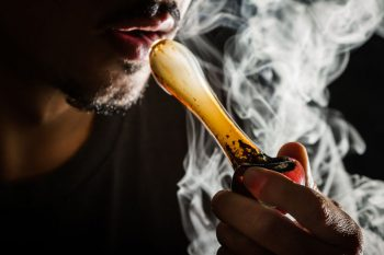 32384430 - studio shoot with model simulating smoking pot with a pipe in a dark high contrast image