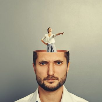 30769269 - displeased businessman with open head. young smiley businesswoman standing into his head and showing the direction. photo over grey background
